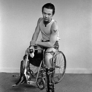 Photograph: a youngYoung man in a wheelchair with the left foot on the floor. He stares into the camera with a direct gaze and holds a coors beer in his right hand. He wears a wife beater t shirt and cut-off levis so that we see his leg braces and tattoo of a bird on his left arm.