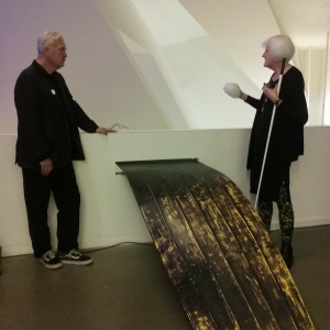 The other side of The Enchanted sculpture features a long strip of wooden planking that resembles a boat protruding out from a wall. A man stands to the left and a woman with white hair stands to the right with a cane, holding a white, rubbery object in her right hand