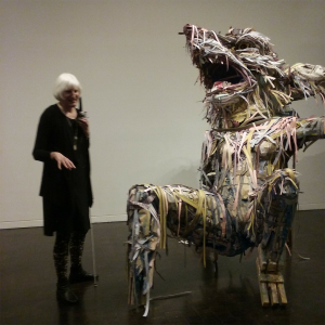 On the left a tall white-haired woman stands dressed in black and holding a white cane, to her right a sculpture made of strips of paper and cardboard of a fox like creature, leaning back on its hind legs and one front leg resting behind its body, appearing to laugh, and towering over the woman.