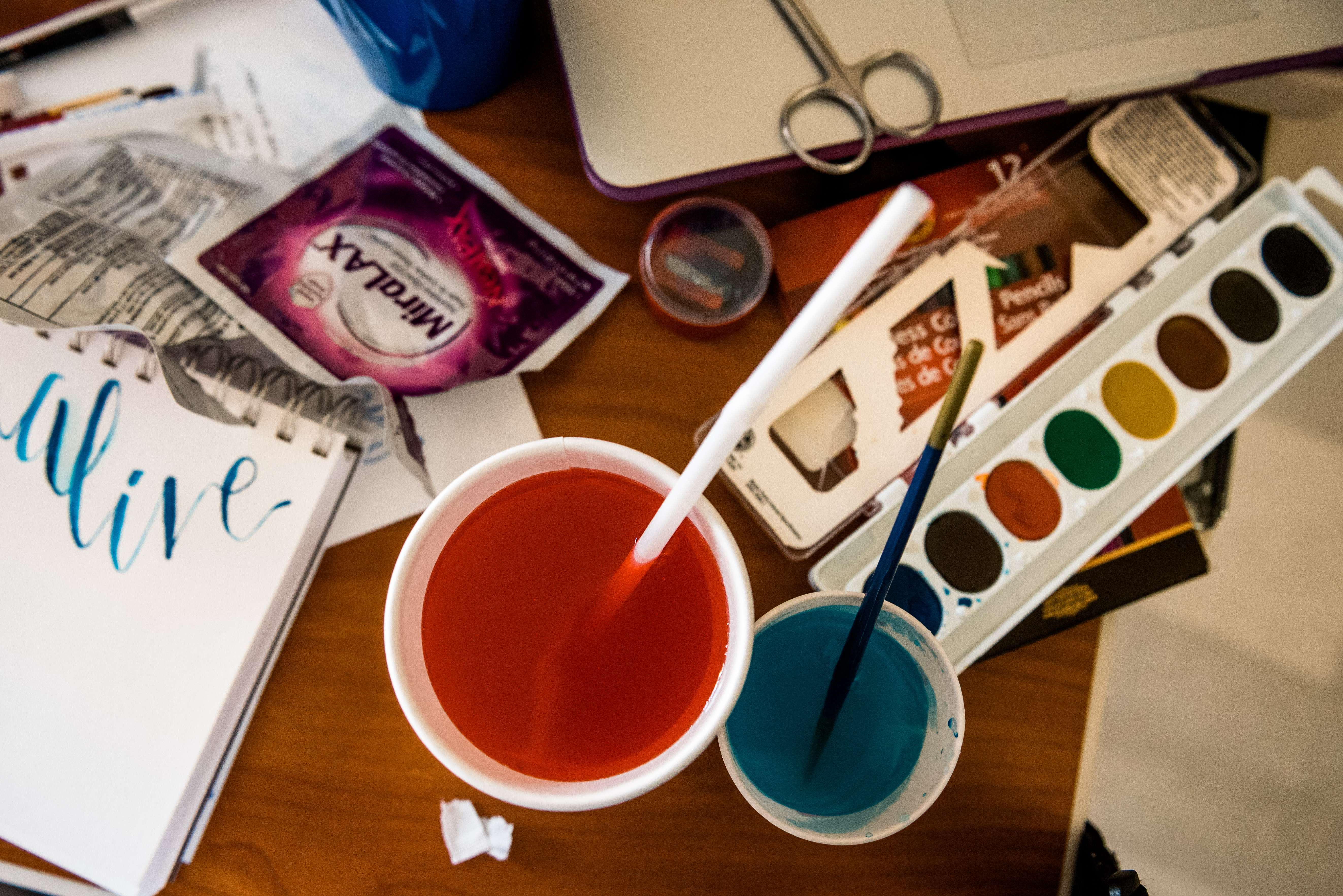 Water color paints, colored water cups with brushes and a sketchpad sit on a table amongst medical wrapper and papers.