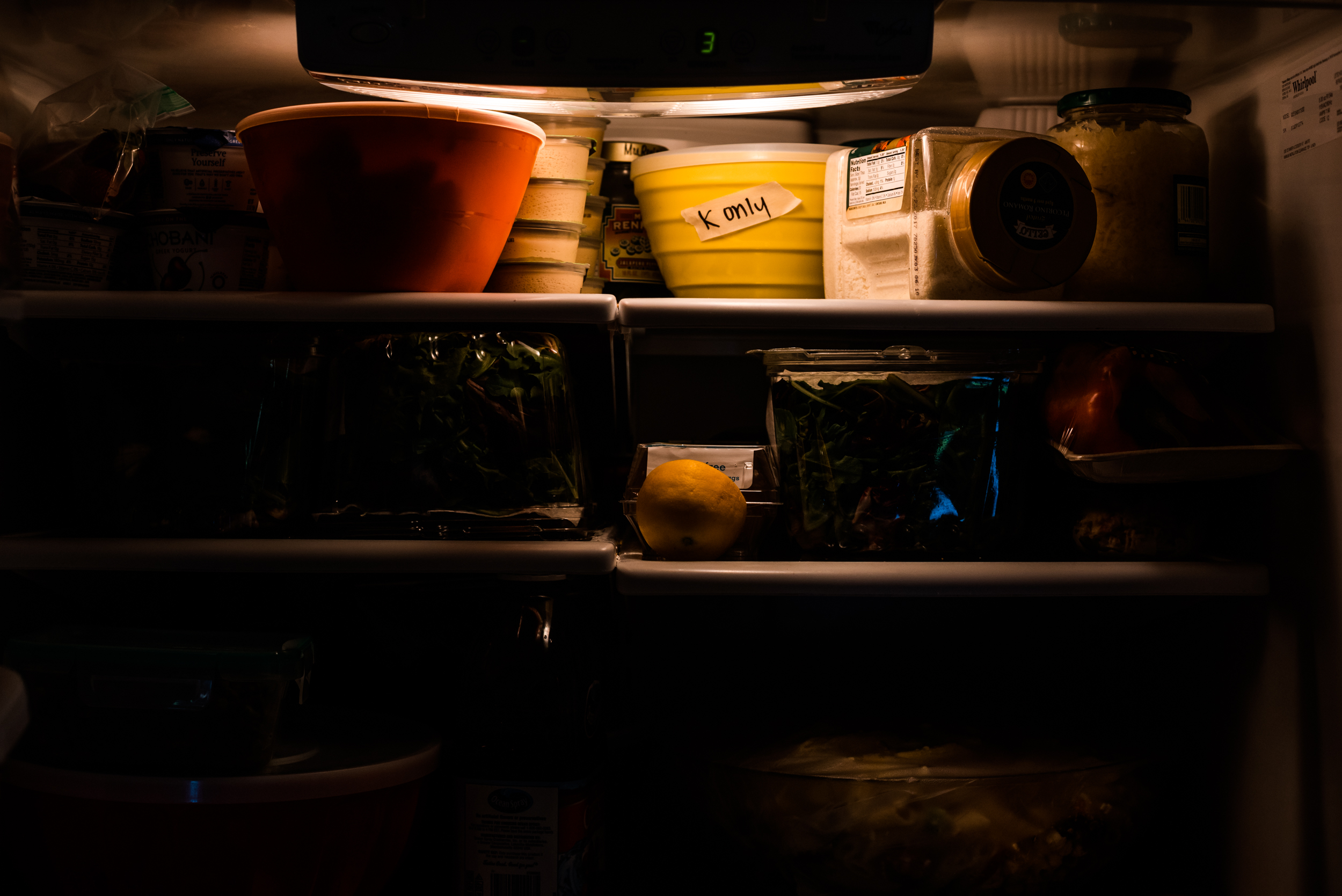 Dark inside of refrigerator shows outlines of containers and light shows yellow container with labeled tape.