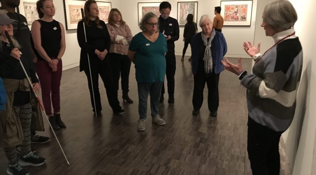 Group of white cane users in art gallery